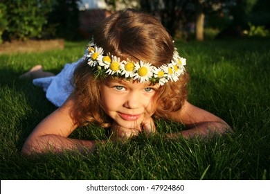 Little girl with wreath of chamomiles