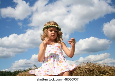 Little girl with wreath of chamomiles on the haystack