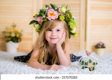 Little girl with a wreath on a head, lying on a white carpet birdcage