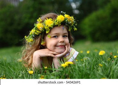 Little girl with a wreath on a head, lying on a glade with dandelions