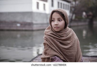 a little girl with a wreath on the head rides on a vintage wooden boat