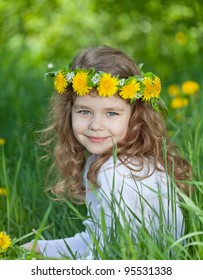 Little girl with a wreath on a head sitting on a glade with dandelions