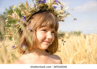 little girl in a wreath of wheat spikelets in the stands in a wheat field