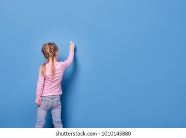 Little girl writes with chalk on blue background
