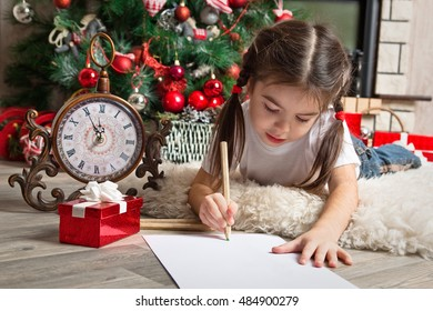 Little girl writes letter to Santa Claus near christmas tree and clock