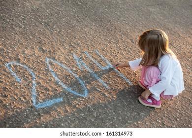Little girl writing 2014 sitting on asphalt