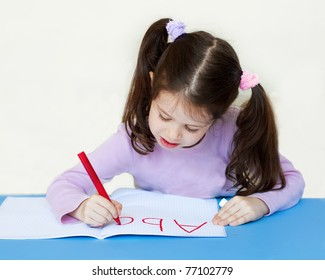 Little girl writing alphabet in a copybook at a desk