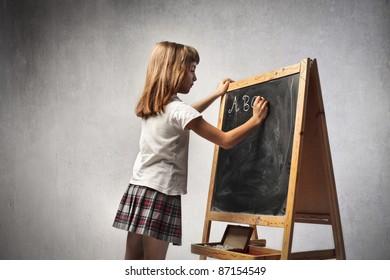 Little girl writing the alphabet on a blackboard