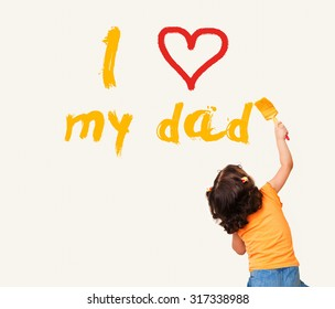 """Little girl writing """"I Love my dad"""" with painting brush on wall background"""