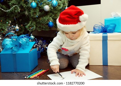 little girl writing a letter to Santa Claus near Christmas tree
