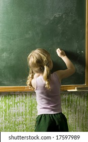 A little girl writing on a chalkboard.  Her back is to the camera.  Vertically framed shot.