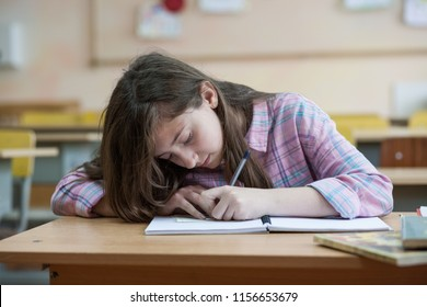 Little girl writing something in copybook and sitting at table