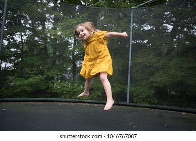 Little girl in yellow dress jumping on the trampoline