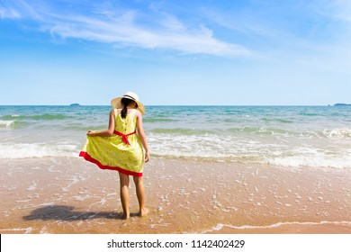 Little girl with yellow dress standing in water on the beach.Children girl relaxing and enjoying peace on vacation.Summer is coming and Summertime concept