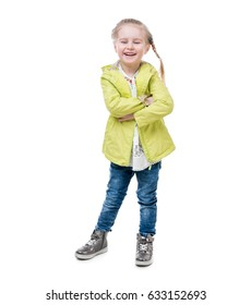Little girl in a yellow jacket, silvery shirt standing, hugging herself, isolated on white background
