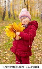 Little girl with yellow leaves in autumn forest