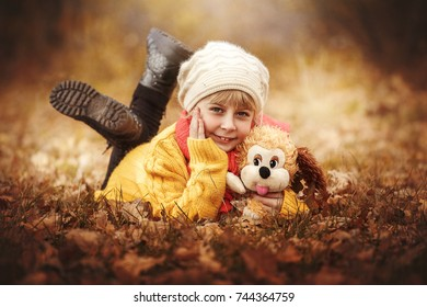 little girl in  yellow sweater and a red scarf lies on  plaid against the backdrop of an autumnal forest and holds a toy plush dog in her hands