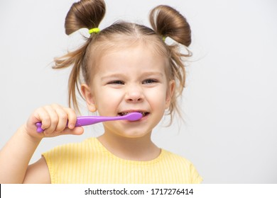 little girl in a yellow T-shirt brushing her teeth clean and smiling, on a light background
