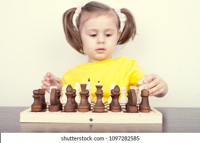 A little girl in a yellow T-shirt is playing chess