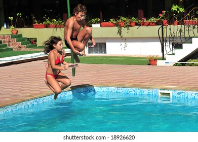 Little girl and young boy jumping in pool