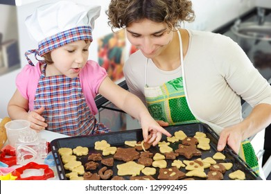Little girl and young mother with baked cookies