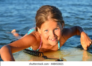 Little girl - young surfer with bodyboard has a fun in the sea