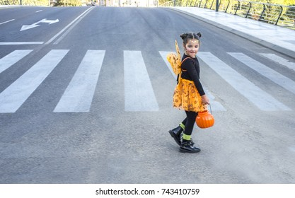 Little girl at zebra crossing in halloween costumes. She is walking towards children party site. Badajoz, Spain