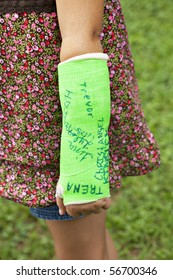 Little girl's arm wearing a neon green cast that has been autographed by friends