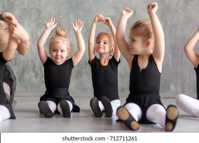 little girls ballerina in black dresses, belk tights and pointe shoes sit on the floor and hold hands over their head for warm-up before teaching ballet in a dancing dark studio