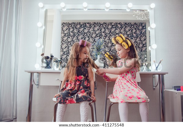 Little girls in beautiful dresses at the mirror