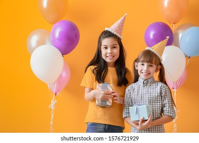 Little girls with Birthday gifts on color background