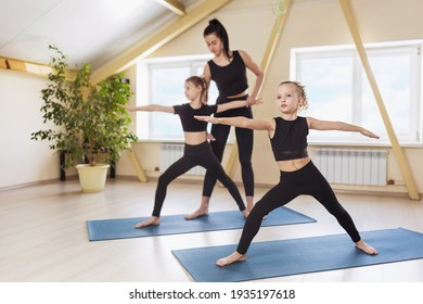 Little girls in black sportswear practicing yoga perform Virabhadrasana, the warrior pose, under the guidance of their trainer. Group training concept.