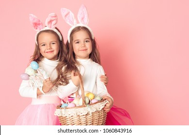 Little girls in bunny ears studio isolated on pink wall easter celebration hugging holding basket with eggs and eggs on sticks togetherness