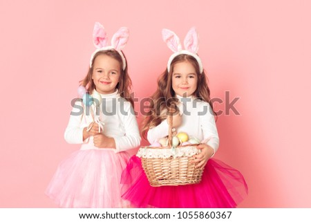 0d52d17c5b Little girls in bunny ears studio isolated on pink wall easter celebration  holding basket with eggs