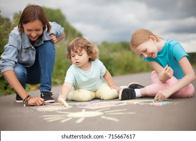 Little girls chalking at the asphalt with elder sister or nanny. Sisters friendship, caring elder sister. Kids in kindergarten. Preschooler leisure time. Babysitting with two kids, young babysitter.
