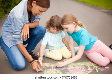 Little girls chalking at the asphalt with elder sister or nanny, friendship, best friends, happy family, kindergarten. Drawing with color chalk. Babysitting with two kids, young babysitter.