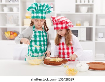 Little girls with chef hats preparing a cake in the kitchen