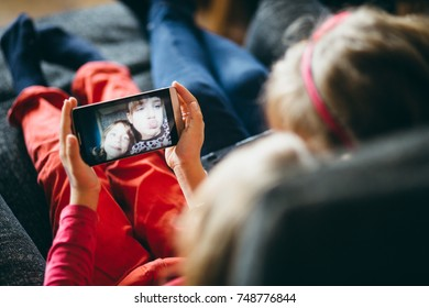 Little girls children kids using phone to look at their selfies