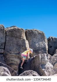 Little Girls Climbs Large Lava Rocks in Hawaii