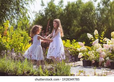 Little girls dancing among wonderful blooming flowers