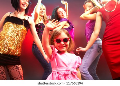 The little girl's dancing in a disco surrounded by big girls