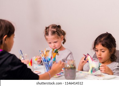Little girls decorating small paper mache unicorn figurines.