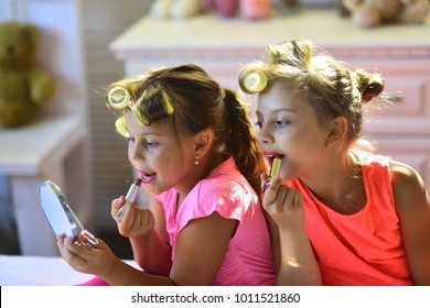 Little girls do makeup sitting in room. Girls with curlers play with makeup accessories in childroom. Beauty and kids fashion concept. Children sit on bed with lipsticks and look in hand mirror.