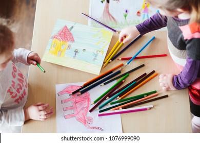 小女孩画一个丰富多彩的图片大象和玩儿用铅笔蜡笔站在桌子室内。 从上面拍摄