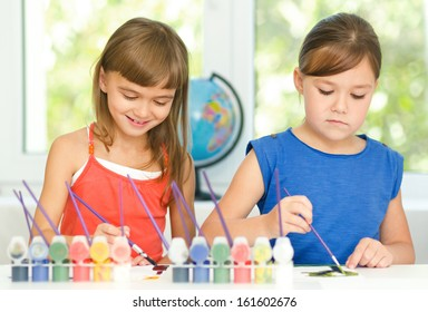 Little girls are drawing using color pencils while sitting at table