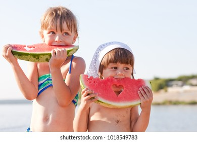 Little girls eat watermelon on the beach