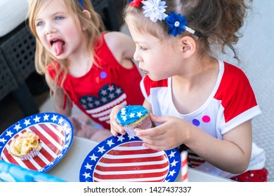 Little girls are eating cupcakes at July 4th party.
