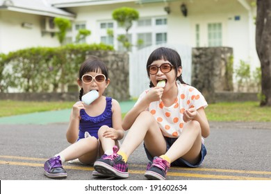 little Girls  Eating Ice Cream and sitting before their house