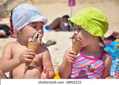 Little girls eating ice-cream on the beach