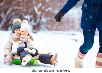 Little girls enjoying sledding. Father sledding his little adorable daughters. Family vacation on Christmas eve outdoors